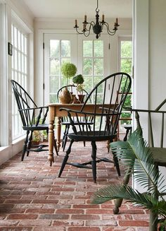 The Connecticut sunroom features sweeping vistas of the lush greenery beyond. Abundant windows allow for easy flow between the indoor space and the garden.