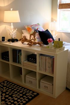 great way to set up a kids room. put toys in baskets, sets apart a nice play space and the shelf gives a little security for bedtime