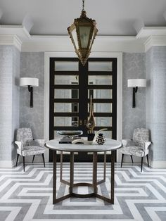 The gray-and-white entrance hall, designed by Jean-Louis Deniot, Inc., features a 17th-century French lantern and a marble floor | archdigest.com