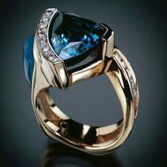 A 12mm trillion-cut Blue Topaz center stone with inlay of pillow-cut blue Gem Silicate with 6 channel-set Diamonds and 6 pavé diamonds - Randy Polk Designs