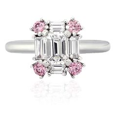 An emerald cut diamond with four intense pink brilliant cut diamonds on the corners, and bordered by four baguette diamonds. These stunning diamonds are set in platinum. A modern design sure to capture the hearts of all.