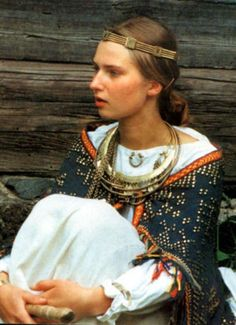 A young woman in a different Latvian folk costume. Brooch she is wearing represents the moon (Mēness).