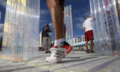 Balazs Baji, an athlete from Hungary, stands on his tiptoes to write on the Olympic truce wall at the Athletes' Village in the Olympic Park during the 2012 Summer Olympics, Friday, Aug. 3, 2012, in London.