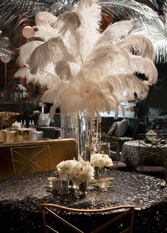 This Great Gatsby inspired tabletop is featuring white feather and sparkle black linens.