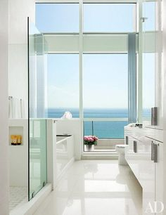 Decorator John Barman raised the ceiling in the master bath of a Miami Beach apartment to a soaring 15 feet. He used the same white ceramic floor tile on the adjacent terrace.