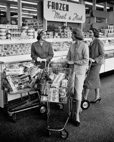 Three stylish 1950s women stop to chat in the frozen meat section of the grocery store.