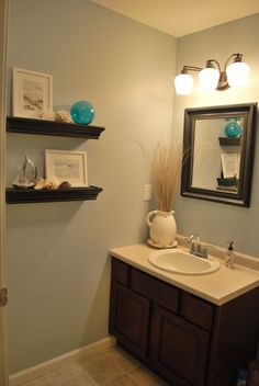 I like the wood tone with the blue walls and beach inspired theme.  Same size bath as mine too.  Do-able.