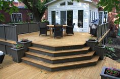 Cascading deck steps adjoin a split-level deck with stylish openness. Notice the deck's custom features including: two toned decking, privacy wall, planters and skirting.