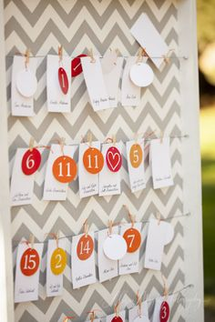 Stylish escort card display. Red, yellow and orange table numbers make the reception seating assignments pop against the grey and white chevron background.