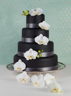 Black wedding cake with fresh orchids. The Sugar Cart Cakes