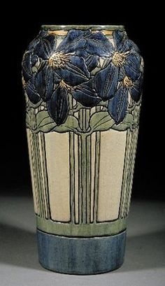 A Newcomb College art pottery high glaze vase from 1904, decorated by Maria de Hoa LeBlanc. It has an incised design of jackmanii climbing clematis in blue, green and yellow underglaze, and the base is marked with the Newcomb cipher, the decorator's mark, and Joseph Meyer's potter's mark. Height: 13 inches.