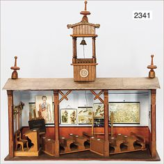 German dollhouse school, circa 1900.   82 cm wide, 77 cm high, 36 cm deep.  Features benches with small porcelain ink drums, teacher's desk, blackboard, a number of billboards, top tower part with bell, cable pull down, roof with lithogr. rrick mottled paper, old painting, inside and outside, 1 window.