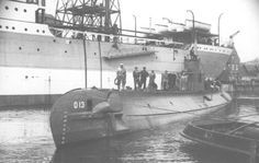 This photo was emailed to us by Miltiades Varvounis and shows the O 13 in what looks like a shipyard. The presence of the yard workers on the deck could indicate this image was taken during the construction, or a refit, of the submarine. The date and place are unknown and we also do not know the name of the ship in the background.