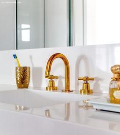 Detalhe do banheiro com torneiras tingidas de dourado a pedido da moradora