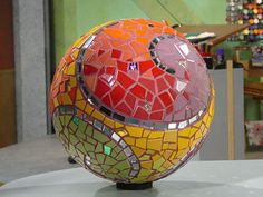 Garden Sphere Mosaic from DIYnetwork.com   This is a fairly complex project starting with creating a concrete surface over the rubber ball. After that it is a regular mosaic project.