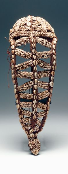 Woman's Fiber Headdress, Papua, New Guinea  Openwork headdress with dome shaped cap and long triangular flap along back. Covered in nassa, cowrie, and conus shells.