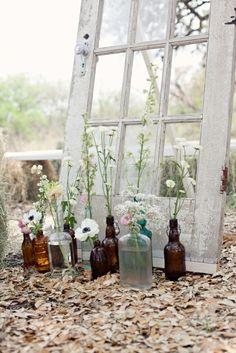 flowers in a bunch of bottles <3