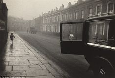 Character: A street cleaner and his cart is framed within the open window of a fancy car, while a street urchin runs along the pavement