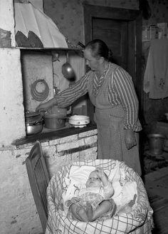 Emäntä puuhellan ääressä | Vahvike Uuden Suomen kummiperheen emäntä laittaa ruokaa. Perheen kuopus kopassaan lieden lämmössä 1940-luvulla. Kehtolaulu (Raita tietokanta). Sotien jälkeen monet tahot järjestivät keräyksiä huono-osaisten hyväksi. Uusi Suomi valitsi kummiperheen, jolle kerättiin rahaa lukijoilta.