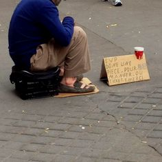 The sign he has may allude to why this man is hoomeless, and shows that it may not be the individuals fault that he or she is homeless.