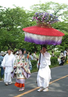aoi-matsuri. A woman dressed in traveling junihitoe along with 2 male attendants,