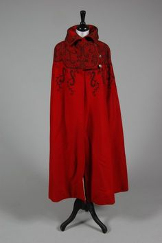 Scarlet wool cape, circa 1890, labelled Cripps & Son, Liverpool, the shoulders and collar adorned with couched black silk and gold thread S scrolls, fronds and vermicular patterns, pierced steel buttons, lined in ivory satin