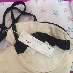 Bathing suit top. White and black, super cute. Still has tags, got it and just never wore it . Has underwire and fits like a bra. Boys + Arrows Swim Bikinis