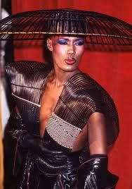 Grace Jones and her trade mark flat top haircut in one of her many incarnations through fashion as living art.