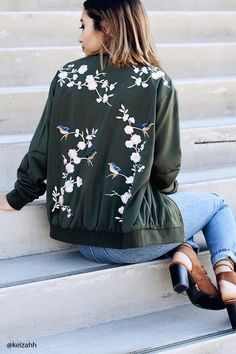 A satin souvenir jacket featuring birds and floral embroidery on the front and back, long sleeves, a basic collar, a zipper front, dual on-seam pockets, and ribbed trim.