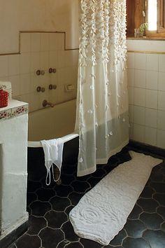 lovely shower curtain + black clawfoot tub + black tile {via anthropologie}