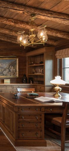 A gorgeous and masculine office in a rustic home with a fireplace as the main focal point | Pearson Design Group #loghomes #logcabins #rustichomes #ranchhomes #rusticbedroom #rusticbedroomideas #loghomelivingrooms #greatrooms #rusticgreatrooms #loghomegreatrooms