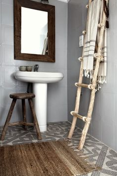 Hotelli Kreikassa - A Hotel in Greece - Grey bathroom with geometric tiled floor, ladder for towels, white pedestal sink - Neutral and natural