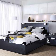 Un dormitorio con una cama MALM en negro y marrón, mueble BESTÅ con puertas amarillas y funda nórdica BOLLTISTEL