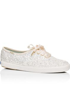 The Keds Glitter Lace Up Sneaker from Kate Spade New York boasts a canvas covered upper in crushed glitter and logo detailing to tongue. The two sets of laces, retro-inspired foxing stripe and cushioned insole complete this statement sneaker.