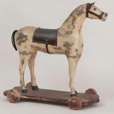 "Painted carved wood horse on platform with wheels.   Saddle and tail ears and bridle /leather, in original paint [ some re-painted areas].   Late 19th century. Size: 20"" long 22"" high"