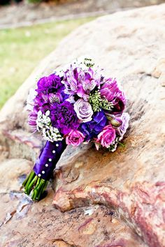 Purple shades of alstroemeria, hydrangea, roses, ranunculus, spray roses, wax flowers and spider chrysanthemums with green seeded eucalyptus for the bridal bouquet! Wedding flowers by Rosie's Floral Boutique. Photography by CnC Moments!