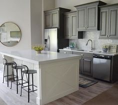 Gray kitchen with island. Wall paint color is Benjamin Moore Edgecomb Gray and the white island is Benjamin Moore Simply White. Gray cabinets are stained in a washed gray. Countertops are Pental Quartz in Lattice. Kitchen stools are Ballard Designs. Mirror is by Lighting Design. Sita Montgomery Interiors