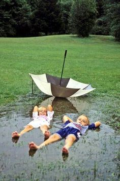Love A Rainy Day. Kids lying in a mud puddle, water puddle actually ditched the umbrella for fun, so cute! I Love Rain, Rain Dance, Under My Umbrella, Rain Umbrella, Singing In The Rain, Little People, Beautiful Children, Rainy Days, Belle Photo