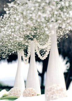 Try spray painting wine bottles white and placing large amounts of baby's breath in bottles. White carnation balls with white orchid on top would be nice at base of arrangement.