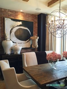 Stunning dining room with black walls, exposed brick, wood beams, and crystal orb chandelier via the Omaha Street of Dreams - Life On Virginia Street