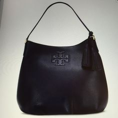 """Tory Burch """"Thea"""" Hobo bag in Navy Leather. NWT Pebbled NAVY Leather Hobo bag is the perfect bag as its comfortable and stylish. On the front has the signature all """"T"""" raised emblem and has matching tassels on the front side of the bag, (removeable) with all gold hardware. This hobo bag is very deep and can hold a lot of your essentials. Inside has 1 large zipper pocket and the opposite side has 3 vertical slip pockets for your smart phone. The top has a zipper closure for added security…"""