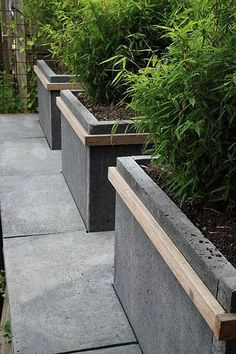 Concrete planters with a nice detail ! Easy project to do : glue concrete pavers together and add wooden strips!!! Bebe'!!! Great idea for garden planters!!! #concreteraisedbeds