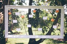 Seating cards pinned to framed chicken wire looks surprisingly pretty, especially for a rustic outdoor affair.