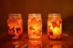 Portavelas con frascos de vidrio y hojas secas