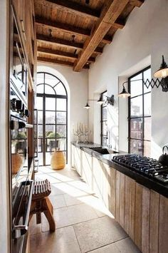 A blend of contemporary and country in the an urban galley kitchen. Great lighting and wooden beams. Wood on the cabinets is a great touch too.