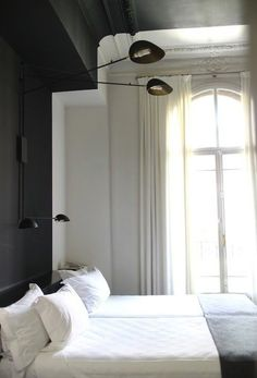 A band of black paint creates a headboard and modernizes the room with 19th century proportions and moldings creatively and inexpensively, at the Praktik Rambla, in the historic Casa Climent Arola building, Barcelona.