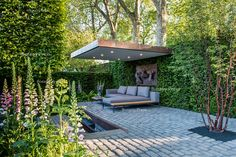The modern patio (entertaining area) with furniture, bronze sculpture, bluestone cobbles, surrounded by Digitalis purpurea, Prunus maackii 'Amber Beauty', Carpinus, Taxus hedging by the garden photographer Joanna Kossak.  Designer: Charlie Albone, Husqvarna presents Support, The Husqvarna Garden, Sponsor: Husqvarna, Chelsea Flower Show, London, UK, 2016