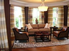 Playing with patterns and textures can liven up any space, as seen in this eclectic living room with plaid drapes, zebra-print rug and striped throw pillows.