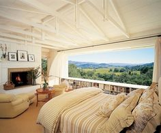 Family photos decorate the mantel in the master bedroom. Backen left the rafters exposed as a nod to farmhouse architecture. An oversize window provides uninterrupted views of the neighboring appellations. Henry Calvin chair, drapery and shade fabrics. Switzer table.