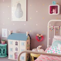Small polka dot vinyl stickers on a brown wall in a girl's bedroom. The polka dots form a pattern and are equidistant from each other.